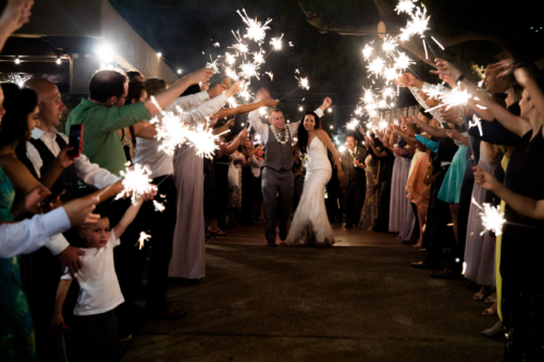 Married couple walking through guests holding sparklers